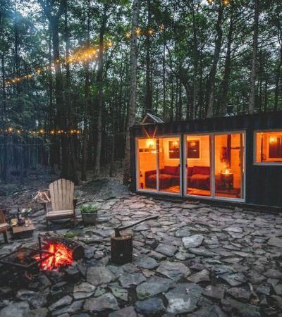 Contêiner é transformado em micropousada com ofurô e fogueira em meio à floresta