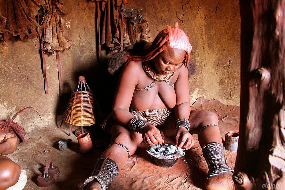 Dentro da moradia principal da tribo Himba, mulher demonstrou como elas tomam banho com fumaça - Foto: Seu Mochilão
