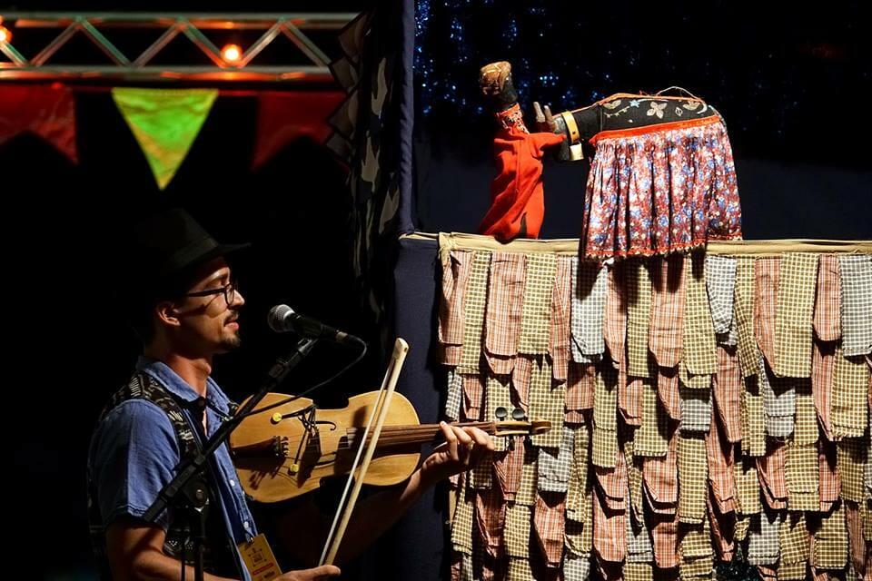 #pracegover Músico toca rebeca, tipo de violino popular, para dois bonecos mamulengos, um negro, de cabelos louros e roupa vermelha e um folclórico boi bumbá