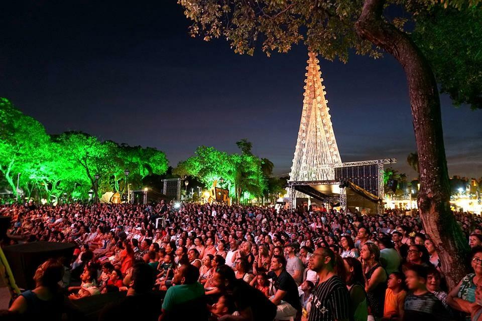 #pracegover Multidão atenda ao espetáculo. Ao fundo, céu anil, árvores do parque e uma grande árvore de Natal ao fundo.