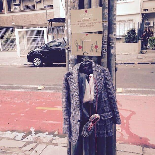 Cabide na rua com um casaco, sapatos e outras peças de roupa