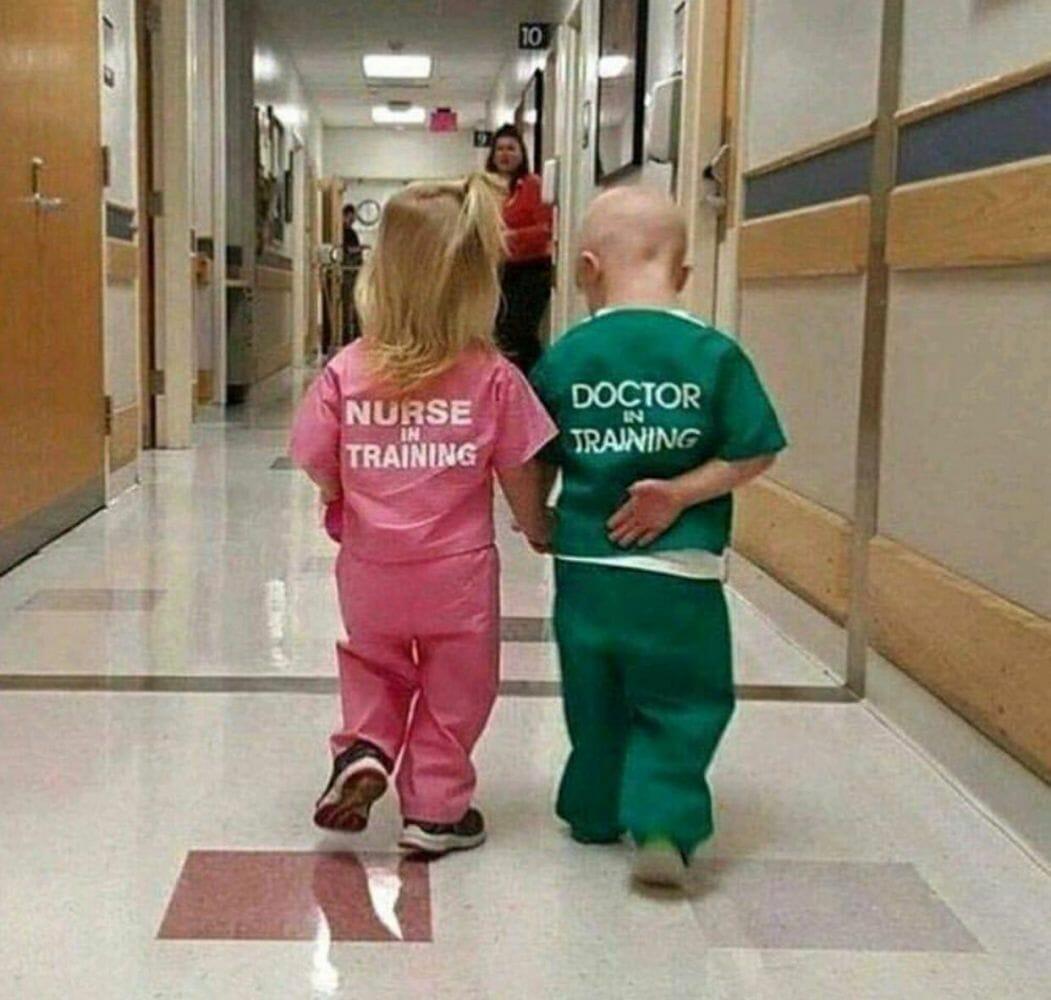 """Duas crianças de costas: menina usa roupa rosa escrito """"enfermeira em treinamento""""; menino usa roupa verde escrito """"médico em treinamento"""""""