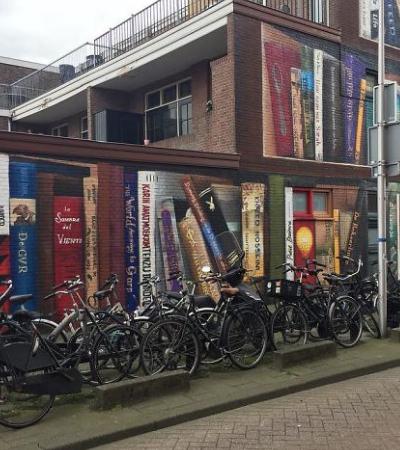 Artistas holandeses pintam a fachada de um prédio com os livros preferidos de seus moradores em tamanho gigante