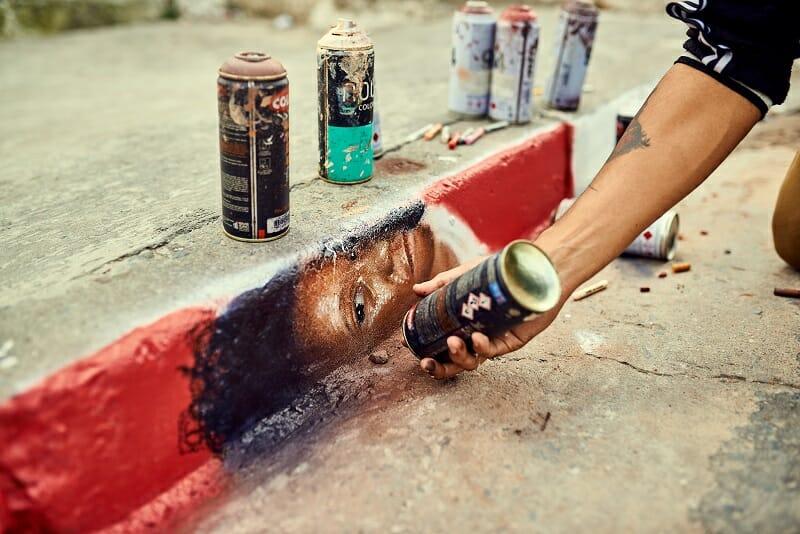Pessoa fazendo um grafitte na calçada