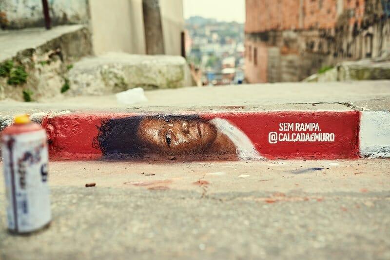 Grafitte pintado em uma calçada com o rosto de uma mulher negra sobre um fundo vermelho