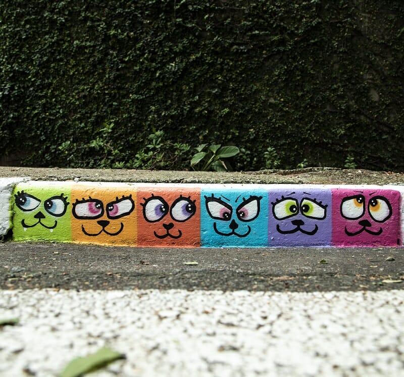 Graffiti pintado em uma calçada mostra a cara de diversos gatinhos coloridos