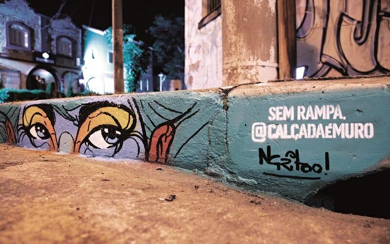 """Grafitte mostra dois olhos e ao lado o escrito """"Sem Rampa, @CalçadaéMuro"""""""