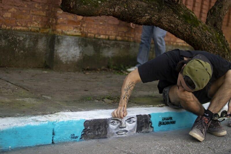Pessoa finalizando um graffite que mostra o rosto de uma mulher pintado no meio-fio