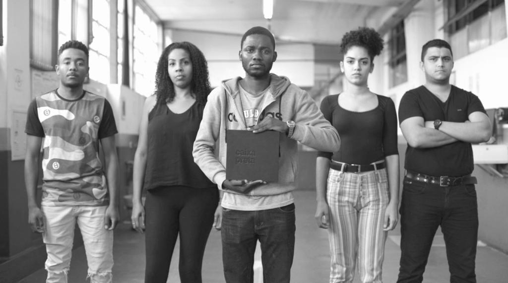 """Cinco jovens negros posam lado a lado, enquanto o que está no centro mostra com o livro """"Caixa Preta"""""""