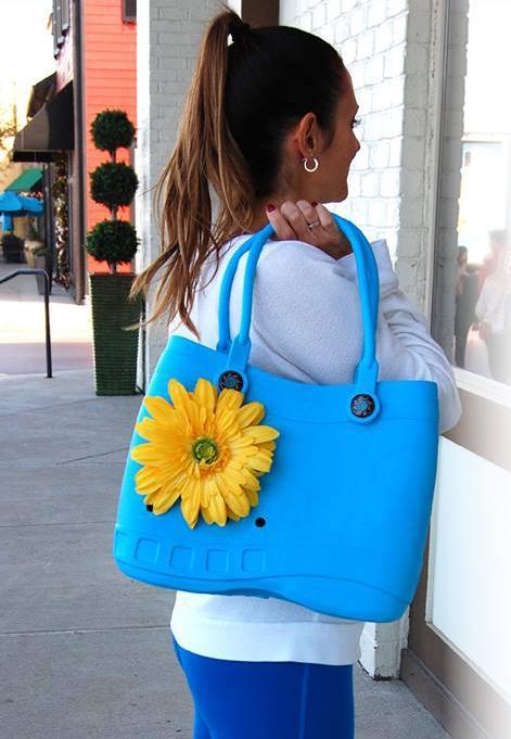 Mulher posa com bolsa azul semelhante ao sapato Crocs