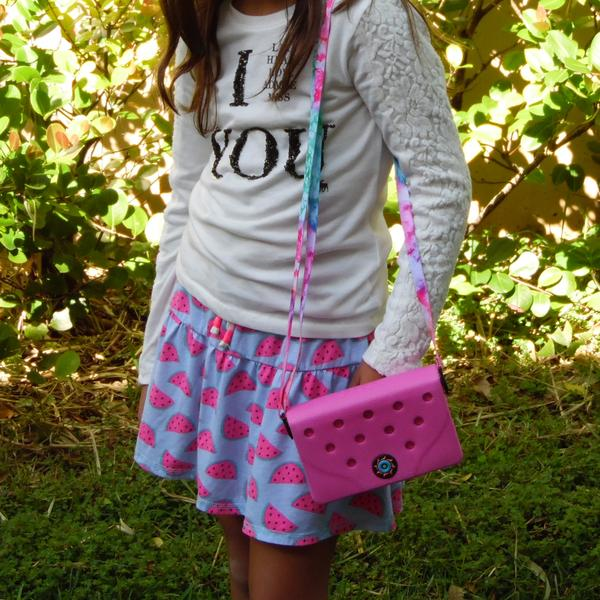 Menina posa com carteira rosa