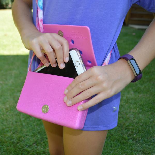 Pessoa coloca um celular em uma carteira rosa