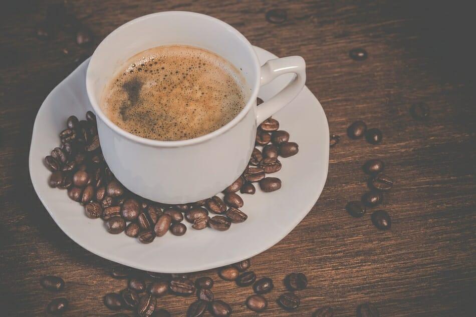 Xícara de café cercada de grãos de café