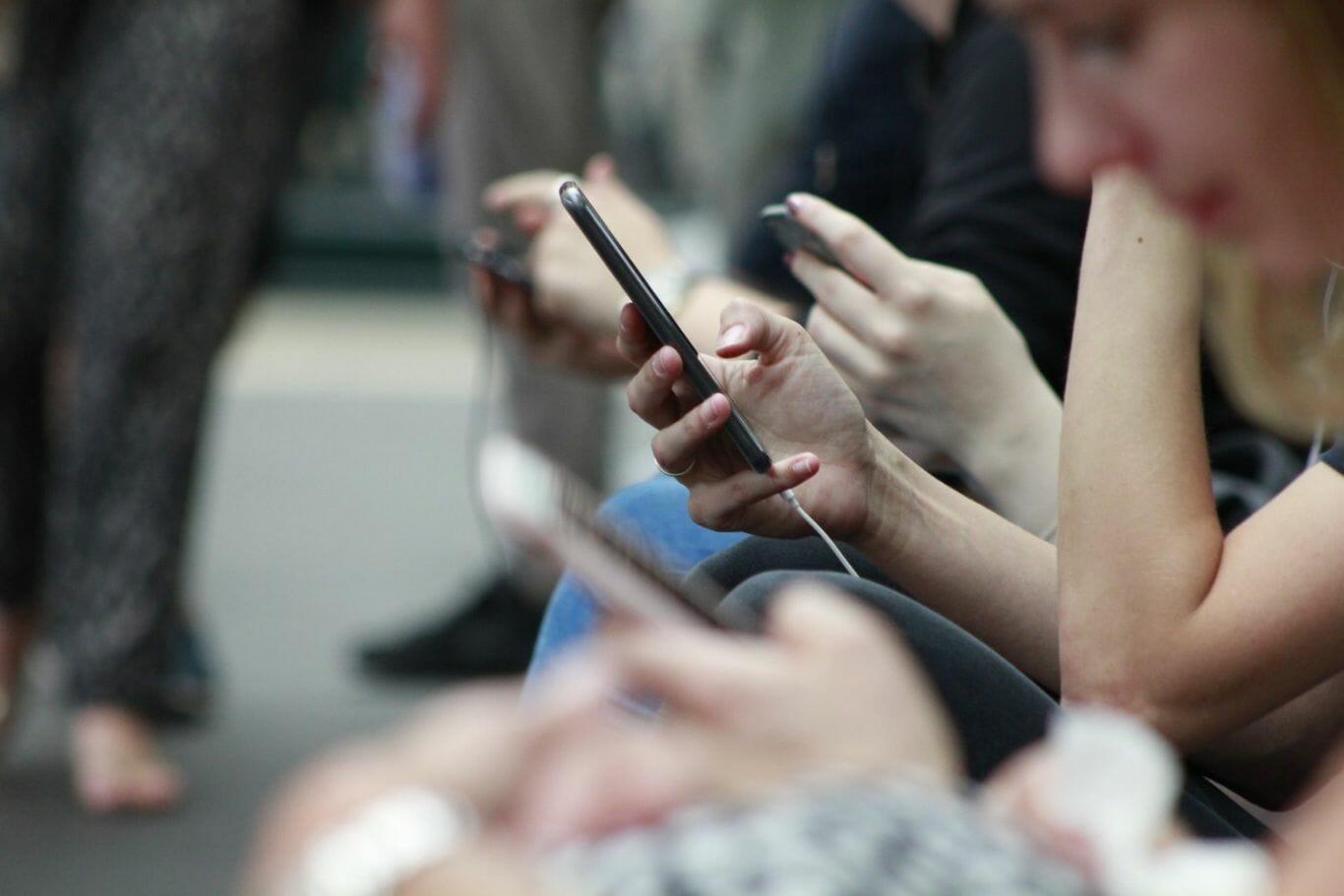 Pessoas conferem celular