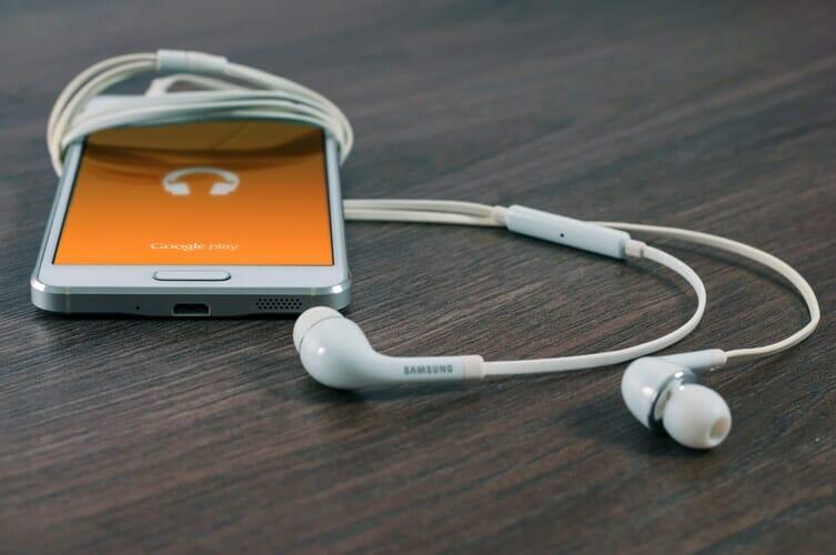 Smartphone com aplicativo de músicas aberto e fones de ouvido