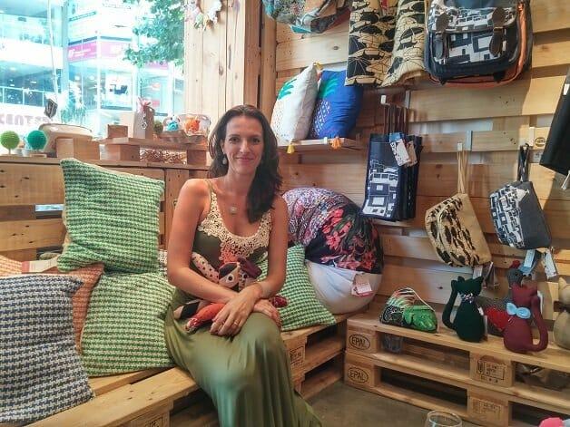 Mulher sentada em um banco de pallets em um ambiente cercado de artesanato