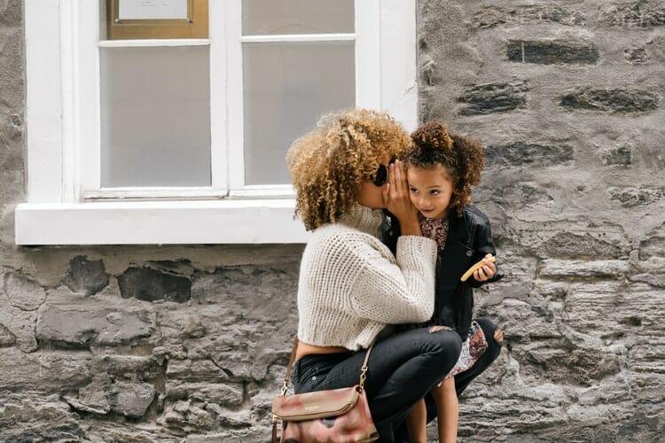 Mulher cochicha no ouvido de uma criança