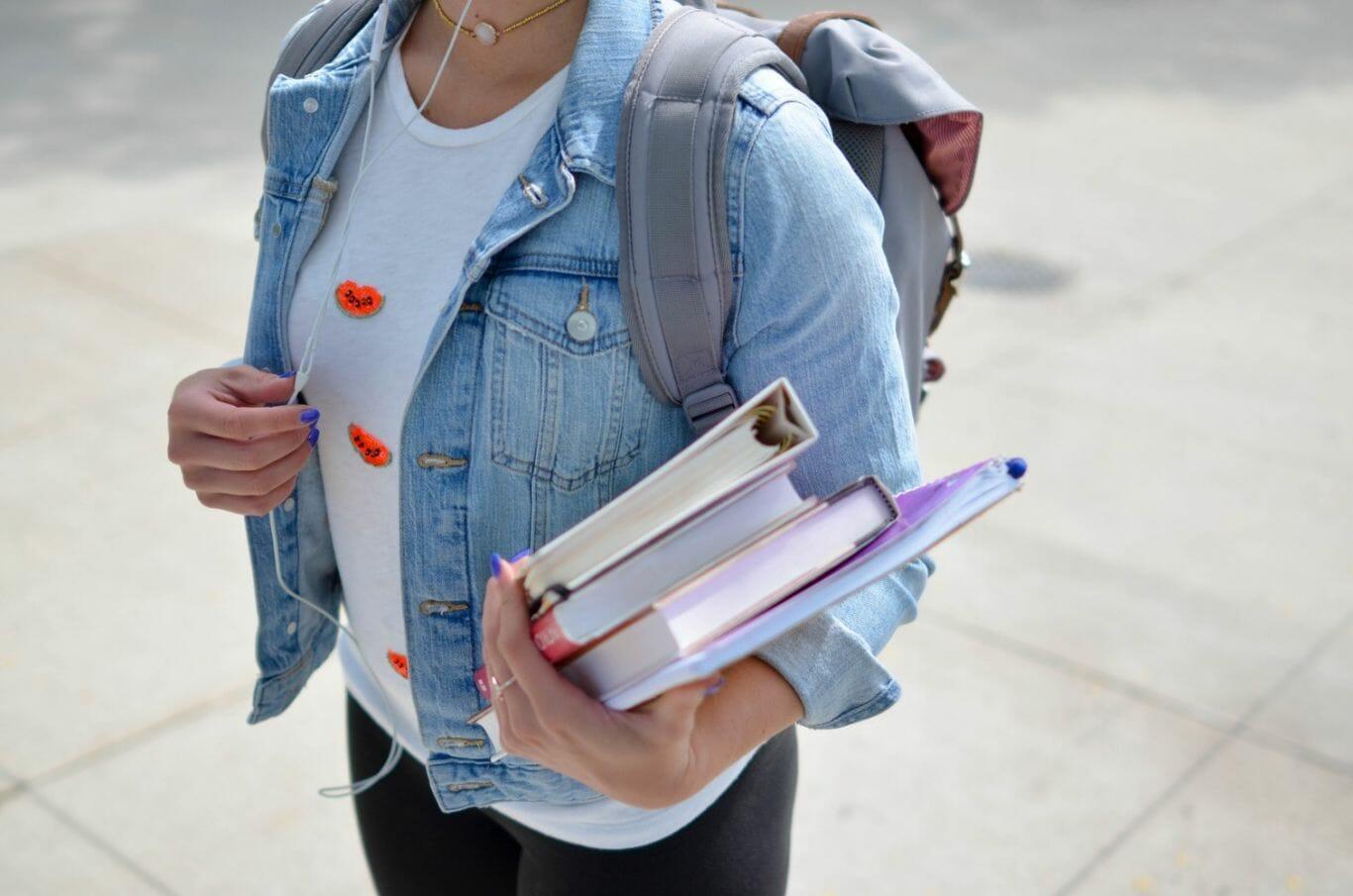 Mulher estudante carrega livros na mão e uma mochila nas costas