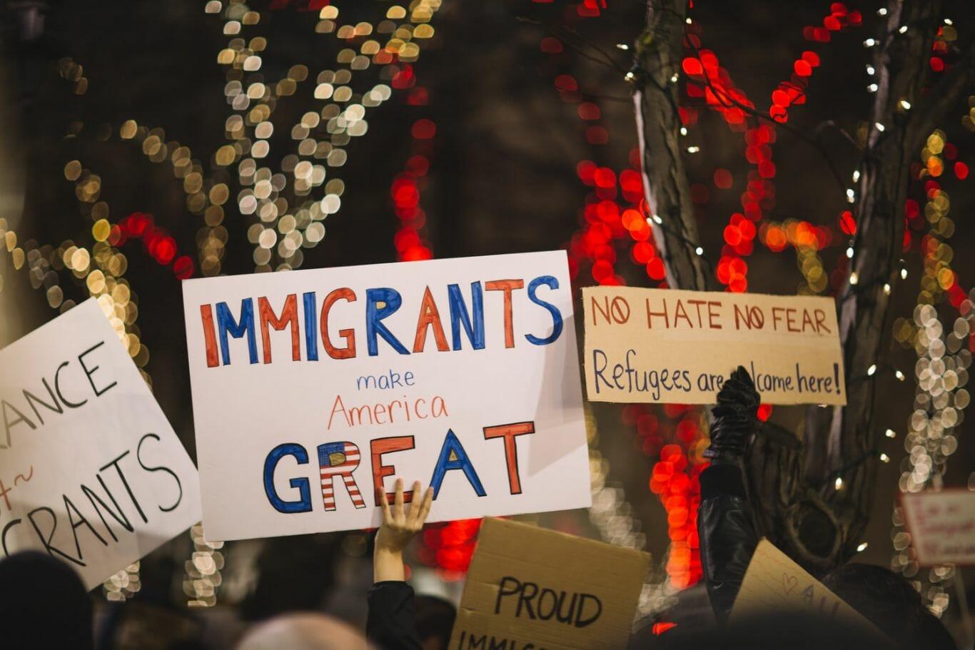 """Pessoas seguram placas com os dizeres em inglês: """"Imigrantes tornam a América grande"""" e """"Sem ódio ou medo, refugiados são bem-vindos aqui"""""""