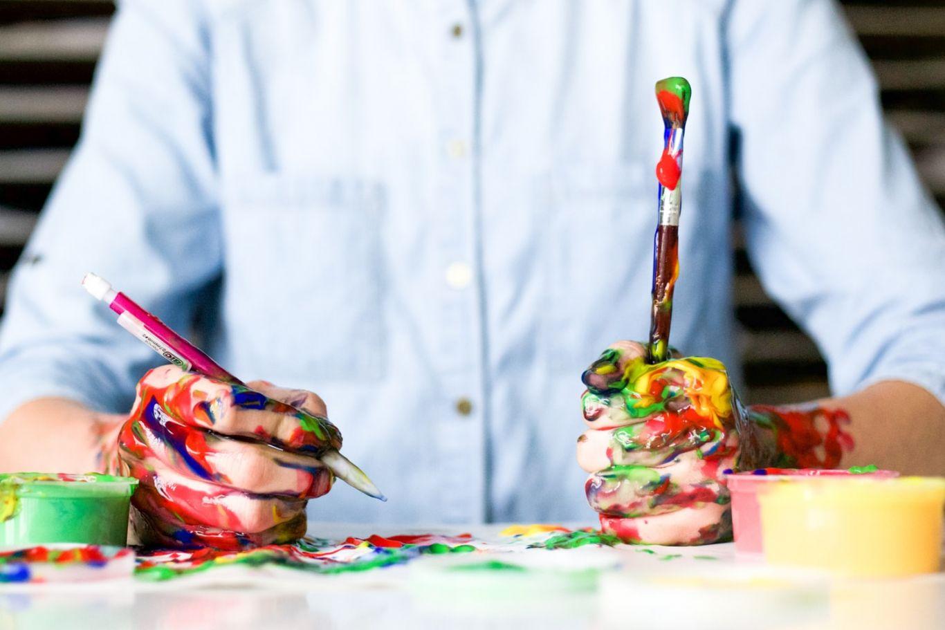 Pessoa com camisa social segura um pincel sujo de tinta em uma mão e uma lapiseira em outra