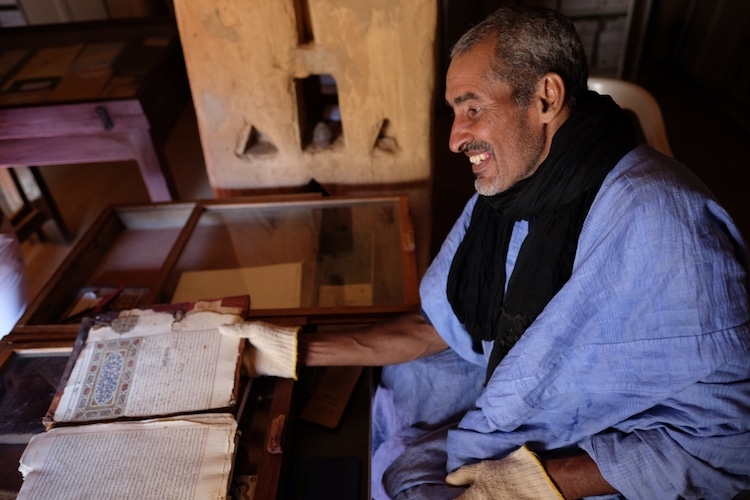 Homem lê livros históricos em Chinguetti, na Mauritânia