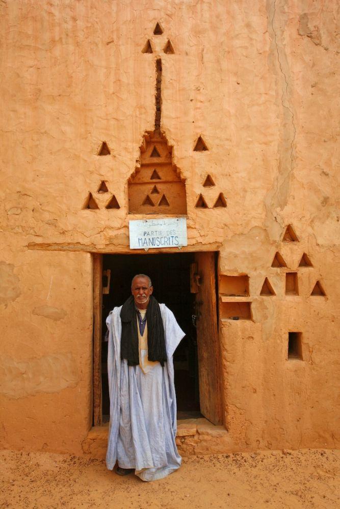 Homem parado em frente a uma porta de biblioteca em Chinguetti, no Saara