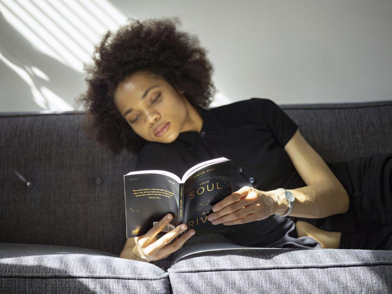 Jovem mulher lendo no sofá
