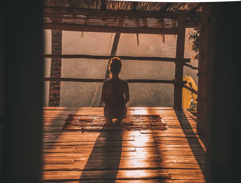 Pessoa ajoelhada de costas em um bangalô como se estivesse meditando
