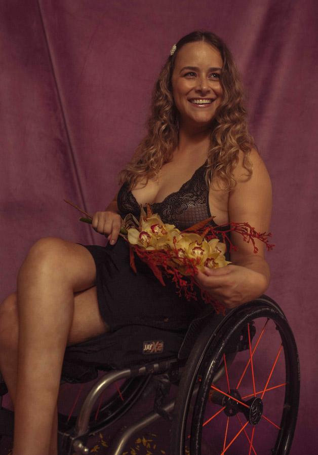Mulher branca, loira de cabelos compridos e cacheados está sentada em uma cadeira de rodas. Ela usa lingerie de renda transparente preta, uma saia preta e está com as pernas cruzadas. Ela está sorrindo, olha para o lado direito e em frente à barriga segura ramos vermelhos com flores amarelas.