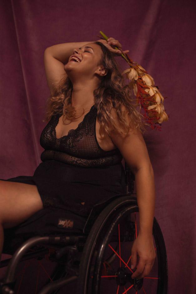 Mulher branca, loira de cabelos compridos e cacheados sorri, com o rosto levantado. Com o braço direito ela segura um ramo vermelho com flores amarelas por cima da cabeça, o outro braço está caído ao lado do corpo. Ela está sentada em uma cadeira de rodas e usa lingerie de renda preta transparente.