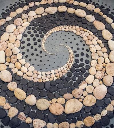 Artista organiza pedras em padrões impressionantes na praia e diz que é terapêutico