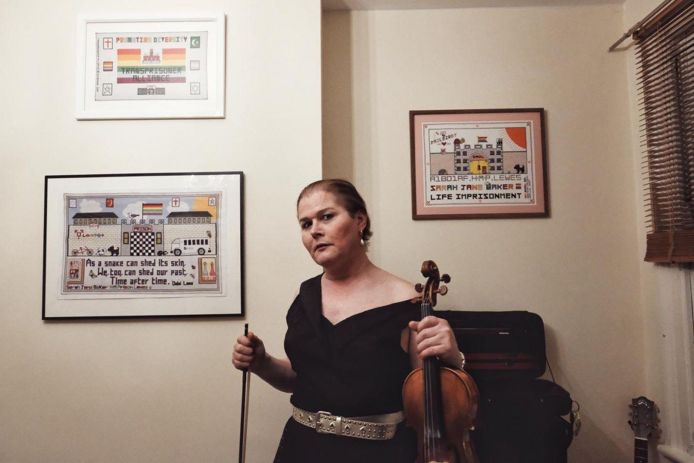 Sarah posa em frente aos seus quadros segurando o violino com a mão esquerda.