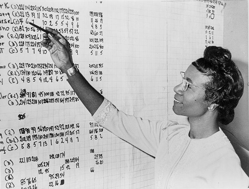 Shyrley Chisholm aparece com uma caneta na mão direita apontando para um quadro branco repleto de números