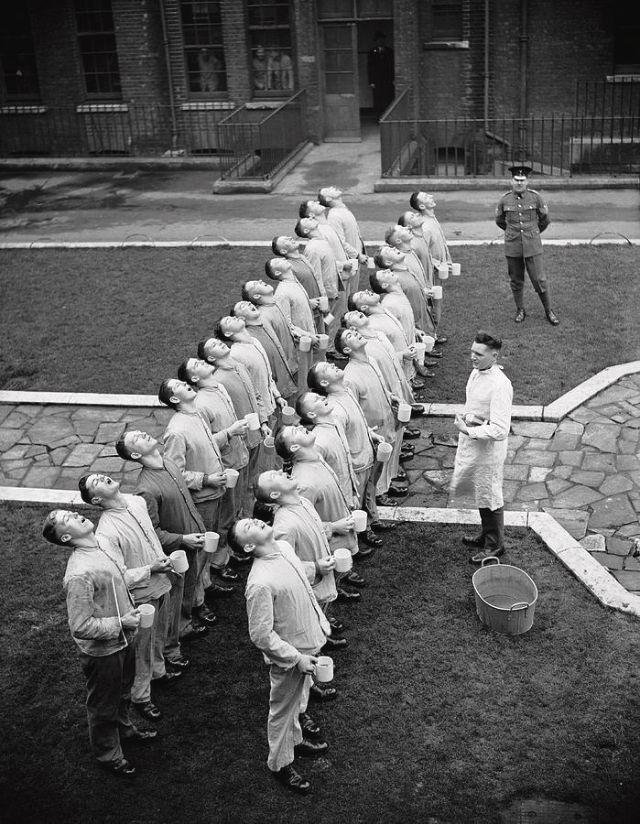 Duas filas de soldados vestidos em roupas brancas gargarejando de frente para o que parece ser um médico