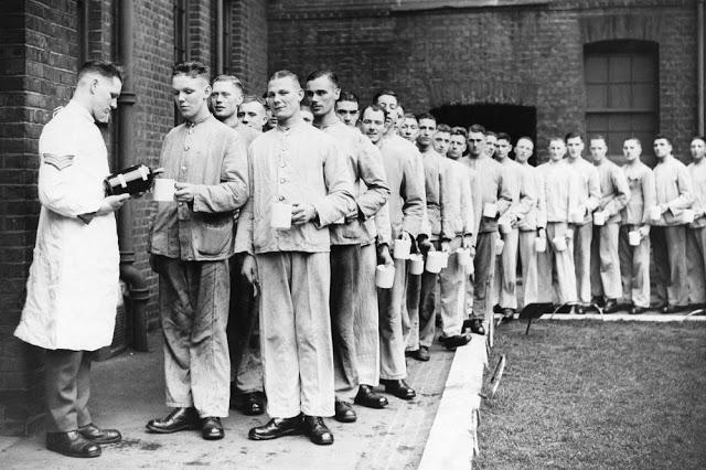 Fila com mais de de soldados britânicos levando suas canecas para que um oficial encha como líquido para gargarejar