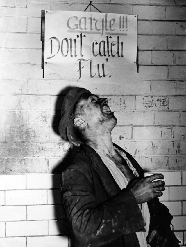 """Homem bastante machucado olha para um cartaz com os dizeres """"Gargareje!!! Não pegue gripe"""""""