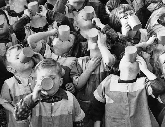 Grupo de crianças com xícaras na boca