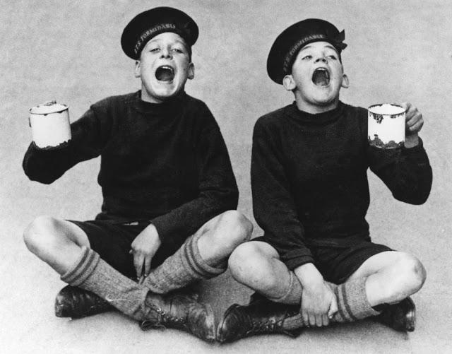 Dois meninos de uniforme escolar gargarejando com canecas na mão