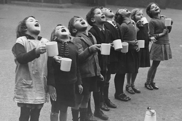 8 crianças gargarejando em fila com canecas nas mãos