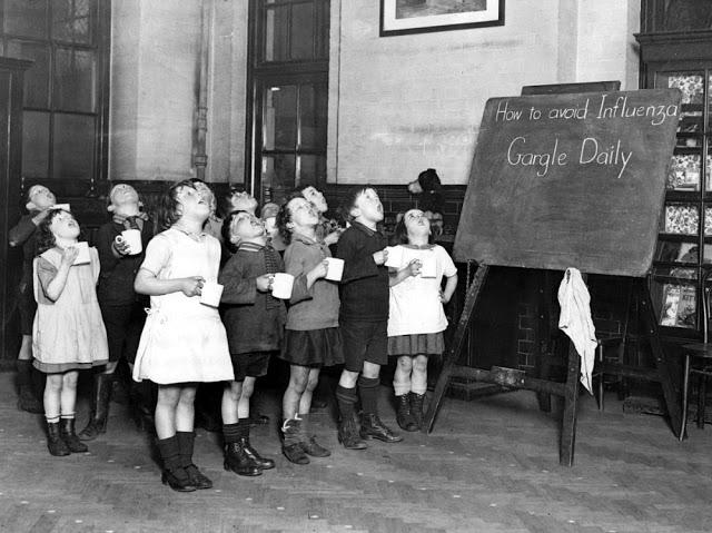 """Grupo de crianças gargareja em frente a um quadro que diz """"Como prevenir a gripe: gargareje diariamente"""""""