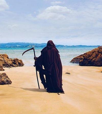 Ele viaja vestido de morte pelas praias que abriram prematuramente