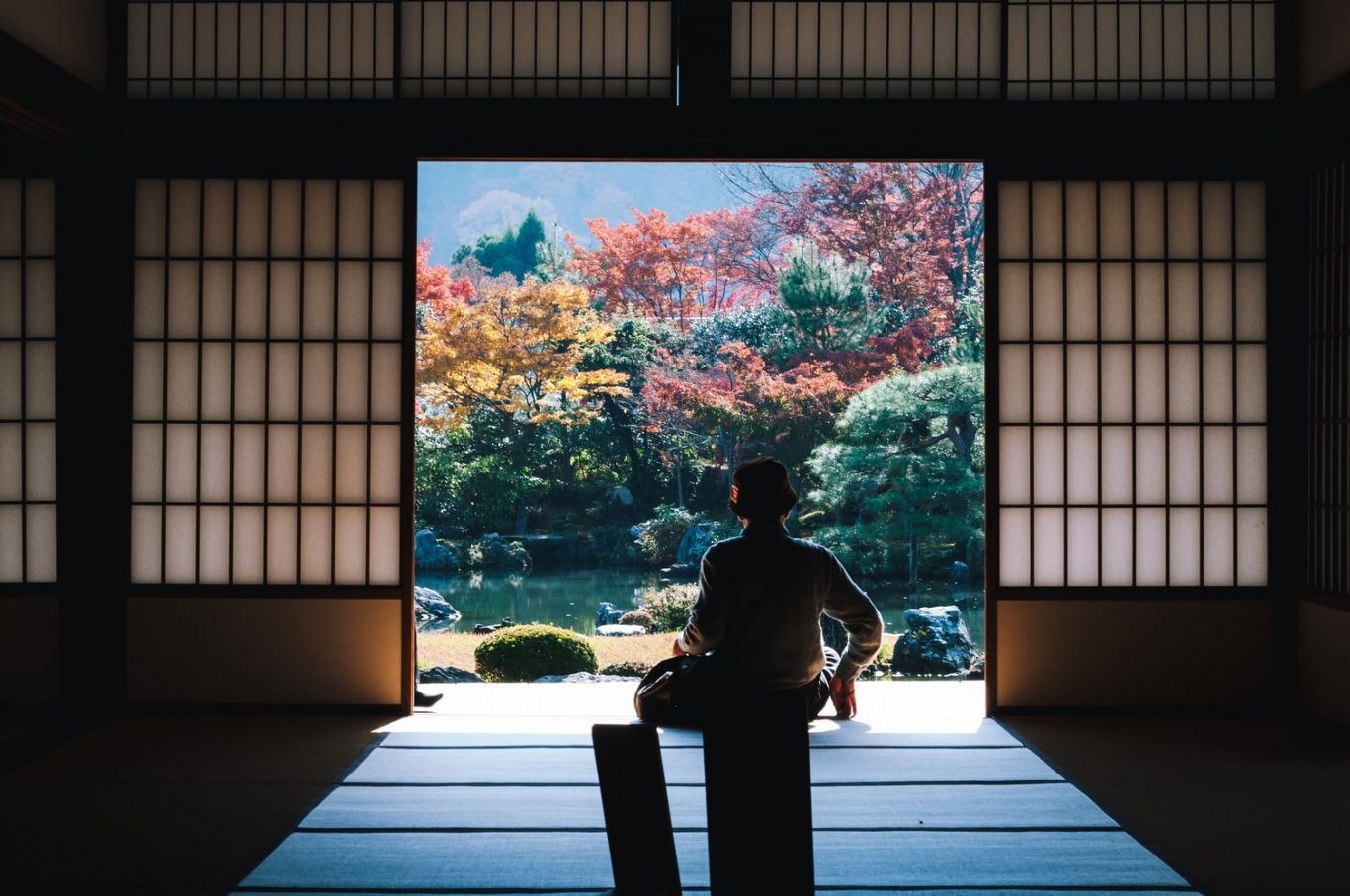 Pessoa sentada em pose de meditação de frente para uma janela