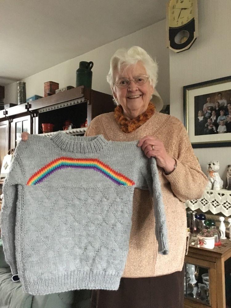 Idosa segura um blusão com um arco-íris tricotado no centro