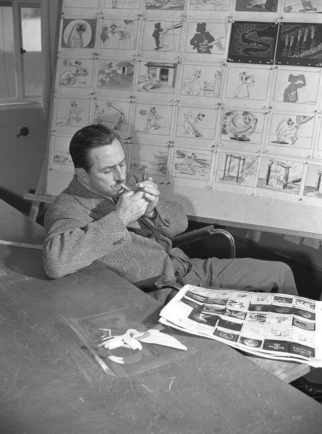 Walt Disney acende um cigarro sentado em frente a um storyboard, em 1945.