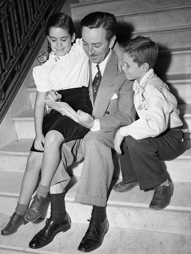 Walt Disney desenhando em um papel sentado em uma escada. Uma menina senta sobre sua perna direita, enquanto um menino está sentado ao seu lado.
