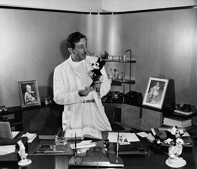 Walt Disney segura uma pelúcia de Mickey Mouse em seu escritório