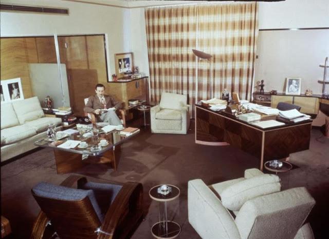 Walt Disney lê sentado em uma poltrona em um escritório amplo decorado em tons de terra