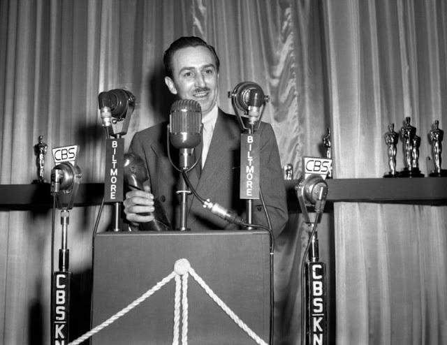 Walt Disney em um púlpito com diversos microfones de empresas de mídia ao seu redor