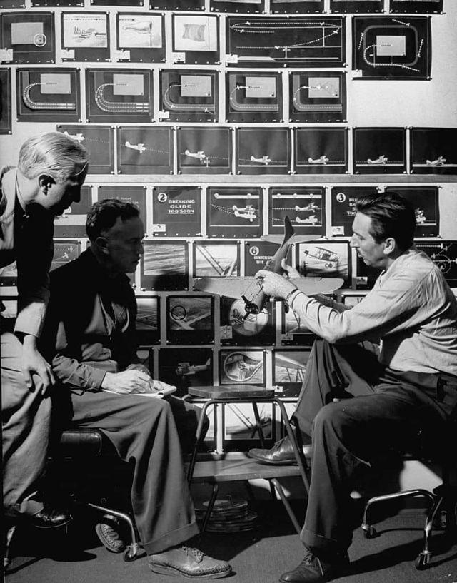 Walt Disney tem um protótipo de avião na mão e está sentado em frente a uma parede com imagens de diversos modelos de aviões. Lt. J.C. Hutchison e outro homem estão sentados em frente a ele.