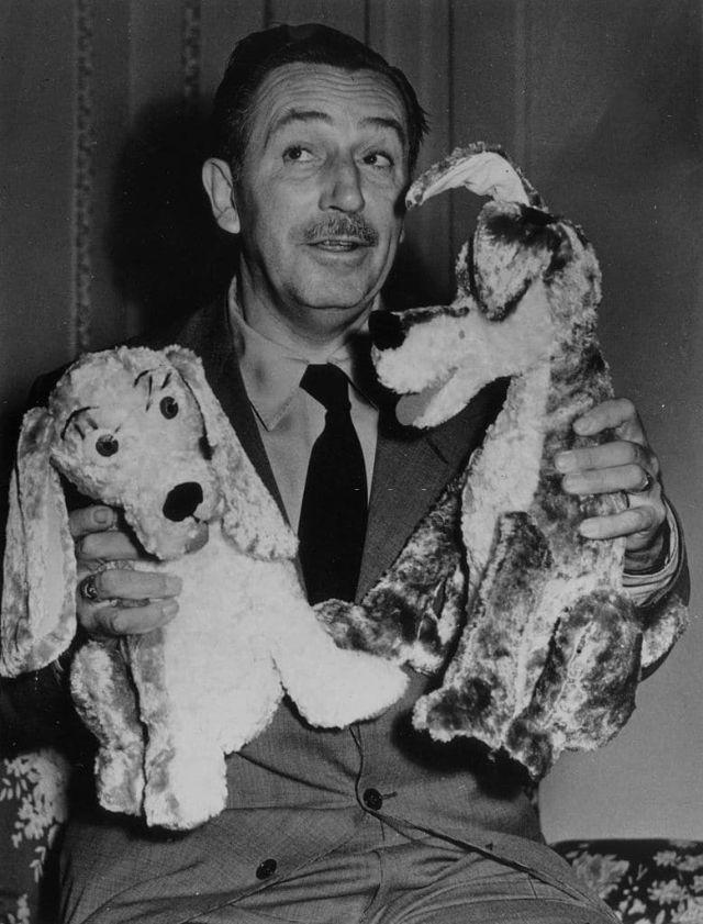 Walt Disney segura pelúcias com os personagens de A Dama e o Vagabundo.